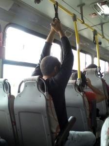 Rapaz sentado segurando na alça para passageiros em pé... Com o ônibus vazio.
